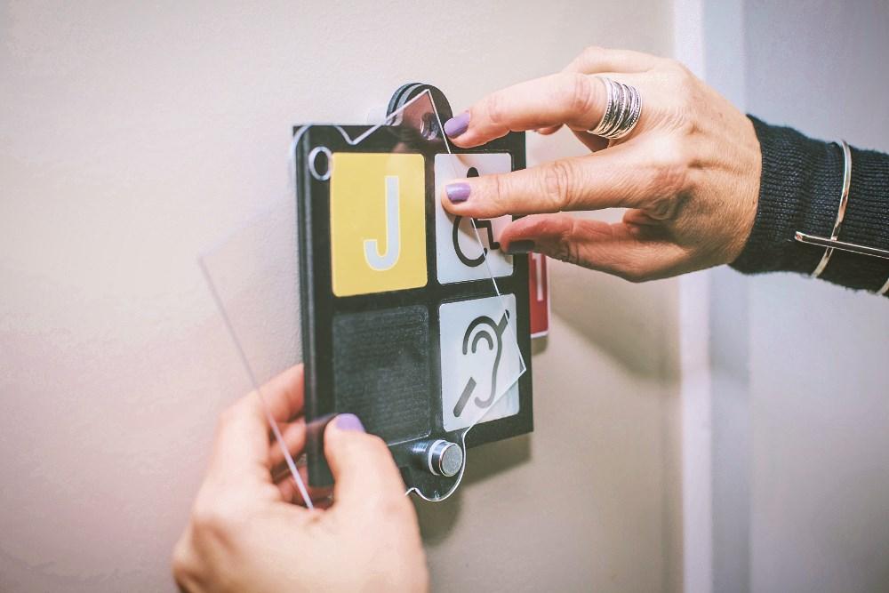 Apposition d'une plaquette signalétique Picto-Sécur à côté de la porte d'un occupant de résidence pour personnes âgées